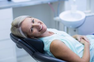 A smiling woman in the dental chair.