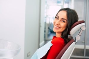 Woman wearing a red sweater sitting in the dental chair smiling