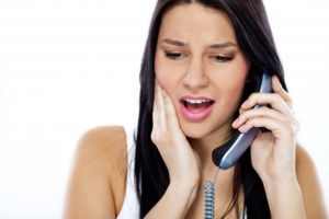 pained woman calling her Lancaster emergency dentist